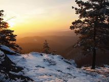 Vue venteuse de matin d'hiver à l'est avec le lever de soleil orange. Aube dans les roches Photos libres de droits