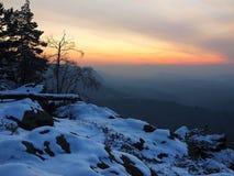 Vue venteuse de matin d'hiver à l'est avec le lever de soleil orange. Aube dans les roches Images libres de droits
