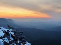 Vue venteuse de matin d'hiver à l'est avec le lever de soleil orange. Aube dans les roches Images stock