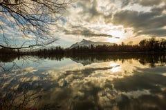 Vue vers les Alpes au-dessus d'un lac au coucher du soleil Images stock