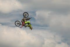 Vuelco de la cabeza del truco del motocrós del estilo libre con la motocicleta en el fondo del cielo azul de la nube Alemán-Stunt Imagen de archivo