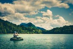 Vuele al pescador en bellyboat que lucha con la trucha grande, Eslovenia imagen de archivo libre de regalías