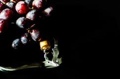 Vuele en espiral con el corcho en caracol al lado de la fruta grande de la uva roja en bla Fotografía de archivo libre de regalías
