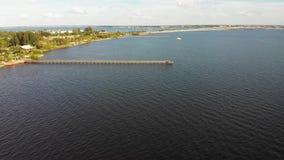 Vuele sobre el océano, el embarcadero y el puente sobre la bahía almacen de video