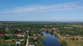 Vuele sobre un campo del verano con las casas y el río metrajes