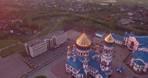 Vuelo aéreo alrededor de la nueva iglesia en pequeña ciudad Templo cristiano y bóveda de oro de la iglesia en el amanecer 4K almacen de video