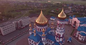 Vuelo aéreo alrededor de la nueva iglesia en pequeña ciudad Templo cristiano y bóveda de oro de la iglesia en el amanecer 4K metrajes