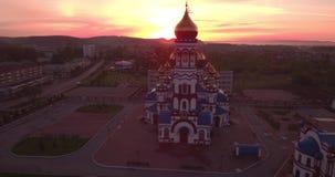 Vuelo aéreo alrededor de la nueva iglesia en pequeña ciudad Templo cristiano y bóveda de oro de la iglesia en el amanecer 4K almacen de metraje de vídeo