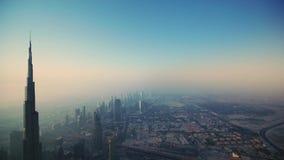 Vuelo aéreo del abejón increíble sobre torres futuristas del rascacielos de la ciudad de Dubai en salida del sol de niebla de la  metrajes