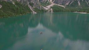 Vuelo aéreo del abejón sobre un Lago escénico di Braies con los barcos en las montañas de las dolomías metrajes