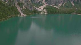 Vuelo aéreo del abejón sobre un Lago escénico di Braies en las montañas de las dolomías almacen de video