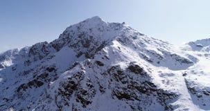 Vuelo aéreo que se mueve adelante sobre establisher nevoso del canto del pico de montaña Scape salvaje alpino de la naturaleza de metrajes