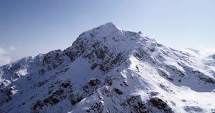 Vuelo aéreo que se mueve al revés sobre establisher nevoso del canto del pico de montaña Scape salvaje alpino de la naturaleza de almacen de metraje de vídeo