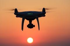 Vuelo accionado por control remoto del abejón en aire y cielo de la puesta del sol Imagen de archivo