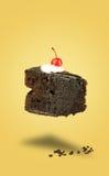 Vuelo aislado de la torta de la cereza del chocolate en fondo amarillo Imágenes de archivo libres de regalías