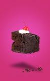 Vuelo aislado de la torta de la cereza del chocolate en fondo rosado Imagen de archivo