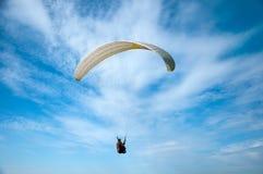 Vuelo blanco del ala flexible en el cielo azul contra la perspectiva de las nubes Fotografía de archivo