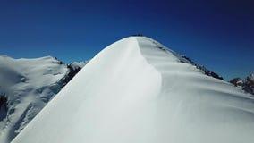 Vuelo cerca del pico nevoso Grupo de escaladores en la cima del pico almacen de video
