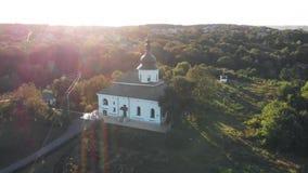 Vuelo circular de la cámara sobre la iglesia en la puesta del sol almacen de metraje de vídeo