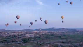 Vuelo colorido sobre las montañas - panorama de muchos globos del aire caliente de Cappadocia en la salida del sol