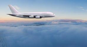 Vuelo comercial del aeroplano de los pasajeros de dos pisos enormes sobre las nubes dram?ticas fotos de archivo