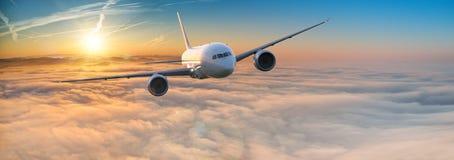 Vuelo comercial del avi?n del aeroplano sobre las nubes dram?ticas imágenes de archivo libres de regalías