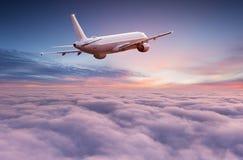 Vuelo comercial del avi?n del aeroplano sobre las nubes dram?ticas imagen de archivo