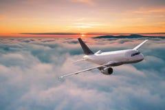 Vuelo comercial del avi?n del aeroplano sobre las nubes dram?ticas imagenes de archivo