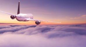 Vuelo comercial del avi?n del aeroplano sobre las nubes dram?ticas imagen de archivo libre de regalías