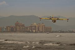 Vuelo contraincendios de los aviones sobre el mar en la playa foto de archivo