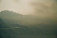 Vuelo contraincendios del helicóptero sobre las montañas Foto de archivo libre de regalías