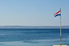Vuelo croata de la bandera en el día ventoso con el mar adriático en fondo Imagenes de archivo