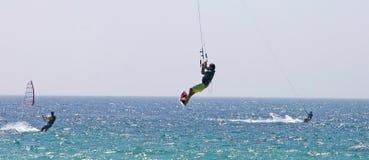 Vuelo de Kitesurfer a través del aire en una playa asoleada Fotos de archivo