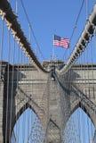 Bandera americana encima del puente de Brooklyn famoso Fotografía de archivo libre de regalías