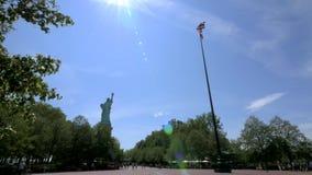Vuelo de la bandera de los E.E.U.U. en Liberty Island con la estatua de la libertad en el fondo almacen de metraje de vídeo