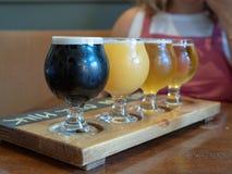 Vuelo de la cerveza de malta, ámbar, cervezas de IPA que se sientan en la paleta de madera fotos de archivo