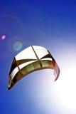 Vuelo de la cometa de las personas que practica surf de la cometa en el cielo azul marino con el sol que emite encendido. Imagen de archivo