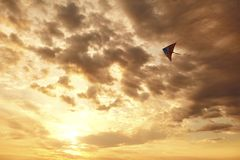 Vuelo de la cometa en el cielo con las nubes en la puesta del sol Fotos de archivo