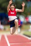 Vuelo de la muchacha del salto de longitud del atletismo Fotos de archivo libres de regalías