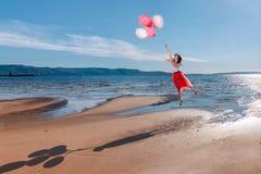 Vuelo de la muchacha en los globos coloreados imagenes de archivo