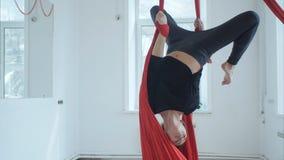 Vuelo de la muchacha y ejercicios agradables el hacer con la seda aérea Imagen de archivo