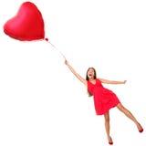 Vuelo de la mujer del día de tarjetas del día de San Valentín con el globo del corazón Fotos de archivo
