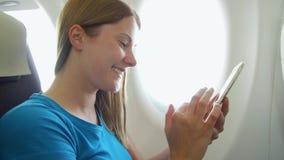 Vuelo de la mujer en aeroplano en d3ia Hembra que usa la ventana cercana relajante móvil durante turbulencia almacen de metraje de vídeo