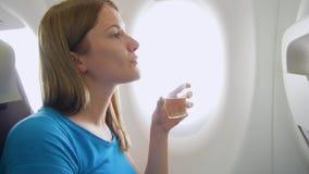 Vuelo de la mujer en aeroplano en d3ia Vino de consumición femenino sediento cerca de la ventana durante turbulencia almacen de metraje de vídeo