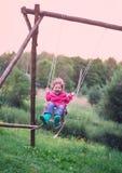 Vuelo de la niña en el oscilación en campo en la puesta del sol Niñez, fotografía de archivo