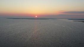 Vuelo de la visión aérea sobre bahía en salida del sol metrajes