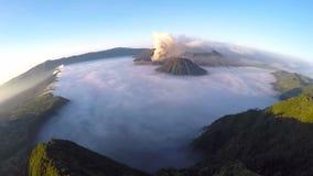 Vuelo de la visión aérea sobre el volcán de Bromo del soporte durante salida del sol almacen de metraje de vídeo