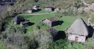 Vuelo de la visión aérea sobre un grupo de casas rurales en las montañas almacen de metraje de vídeo