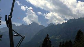 Vuelo de Paraglide en las montañas y el bosque de Dolomiti de una elevación de silla móvil metrajes