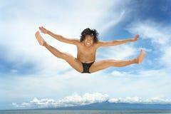 Vuelo de salto del hombre sobre el mar Foto de archivo